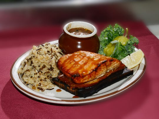 Cedar-plank salmon is served with soy-mustard glaze, wild rice and a mix of beans, onions and corn at Winchesters Grill & Saloon in downtown Ventura.