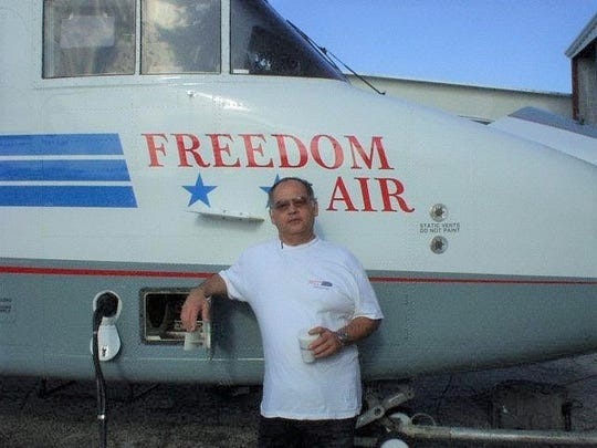 Joaquin Lago Flores Jr., shown in an undated photo provided by Guam Visitors Bureau, with a Freedom Air airplane.