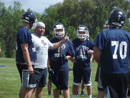 Bay Port football coach Gary Westerman goes over a play with Cole Van Lanen, left, Connor Krah, near right, and Quinn Pierner during Tuesday's practice in Suamico.