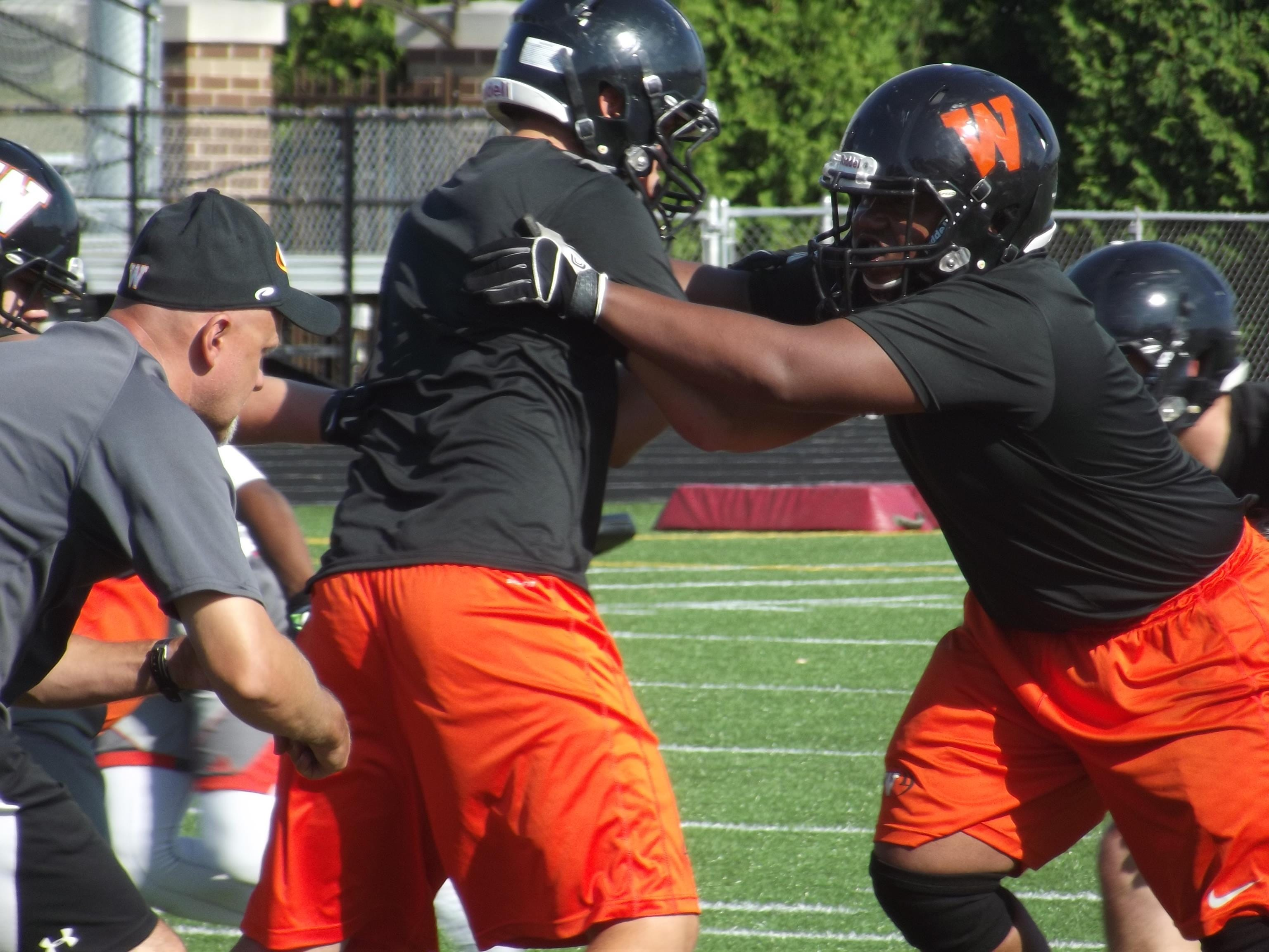 West De Pere senior defensive lineman Malcolm Smalls goes through a defensive drill with coach Jack Batten at practice Wednesday.