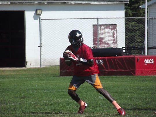 Green Bay East senior Deonte Carlton drops back to pass at practice Wednesday. Carlton is transitioning to quarterback this year.