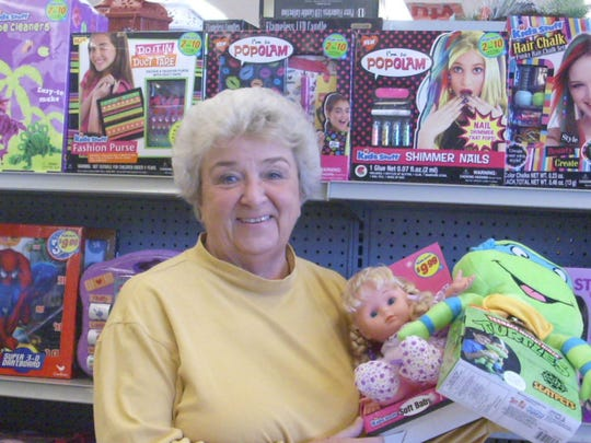 Kay Dick, chairwoman of Caring for Clyde Kids, holds an armful of toys after a shopping trip at Family Dollar in a recent Caring for Clyde Kids holiday giveaway.