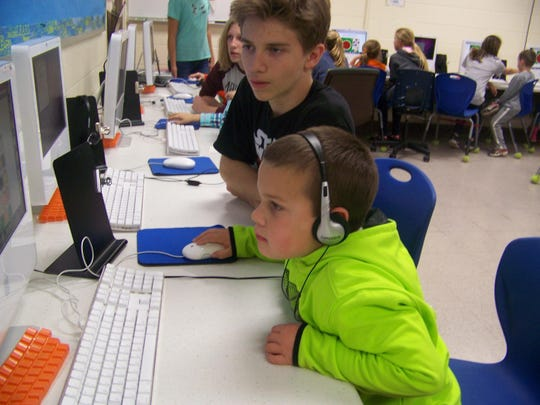 Fox Valley Christian Academy seventh-grade student Mike Ramsey helps kindergarten student Nathan Ney learn some computer skills.