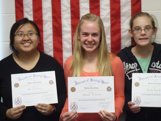Mai Yer Yang, from left, Olivia Nillison and Emily Rose Riedel receive certificates for participating in the audio essay contest sponsored by the Veterans of Foreign Wars. They are students at Northland Lutheran High School.