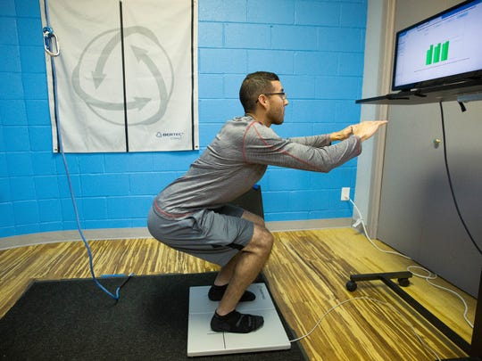 Mark Tovar, a physical therapy technician demonstrates the Bertec System at Southwest Sport and Spine Center. The Bertec system helps diagnose problems in how a person stands and how it can affect their stability and recovery from balance issues.