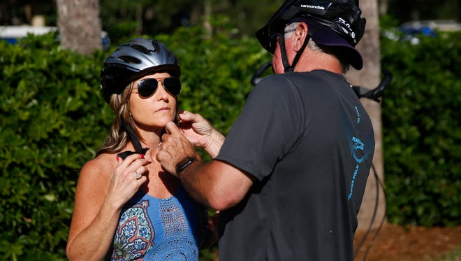 Larry Rydzewski helps his wife, Michelle, with her helmet before riding ElliptiGO bikes on Friday, Feb. 16, 2018, in Pelican Bay in North Naples. The bikes provide a low-impact alternative to running.