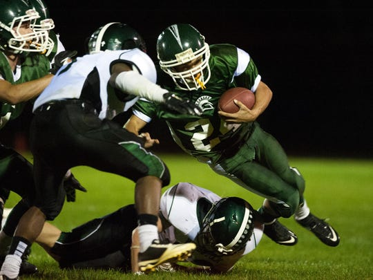 Winooski's Brandon Bigelow (24) is tripped up during the game between the Woodstock Wasps and the Winooski Spartans at Wionooski High School in 2014.