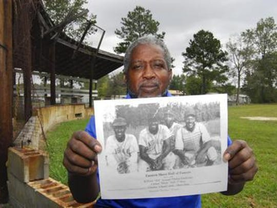 In this September 2008 photo, Kirkland Hall poses at the Oaksville Eagles Ball Park that was home to an all-black baseball team in Oaksville near Princess Anne. He holds a picture of members of the Eagles who were inducted into the Eastern Shore Hall of Fame, including his dad, Charles Hall. The team also belonged to the Delmarva Negro League, which is having its first player reunion at the Oaksville Eagles ballpark on July 26, 2015.