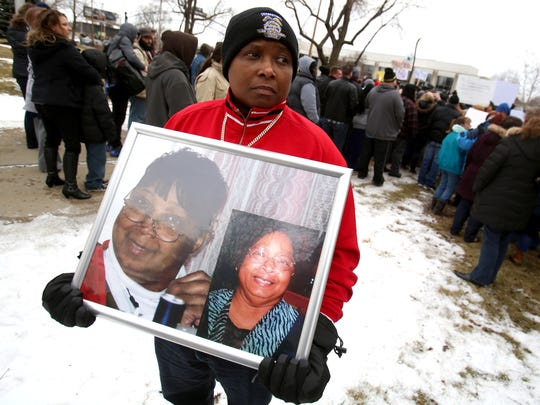 Cholyonda Brown, 42 of Davison holds pictures of her