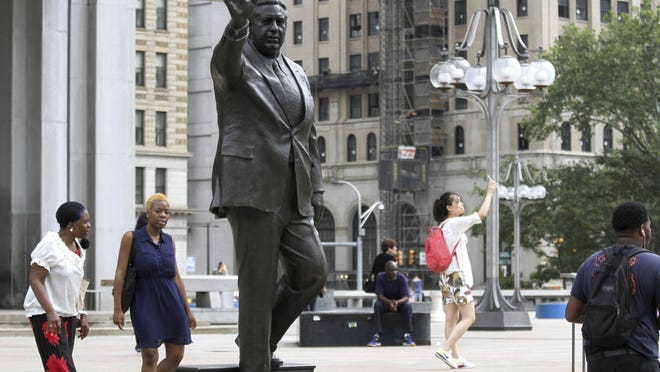 FILE- In this Aug. 10, 2016 file photo, people walk by a statue of late Philadelphia Mayor Frank Rizzo, who also served as the city's police commissioner, on Thomas Paine Plaza outside the Municipal Services Building in Philadelphia. A city councilwoman is leading the push to take down the likeness of Rizzo, considered by some as a tough-talking, tougher-on-crime lawmaker, but to others as a racist, anti-gay bigot. (AP Photo/Dake Kang, File)