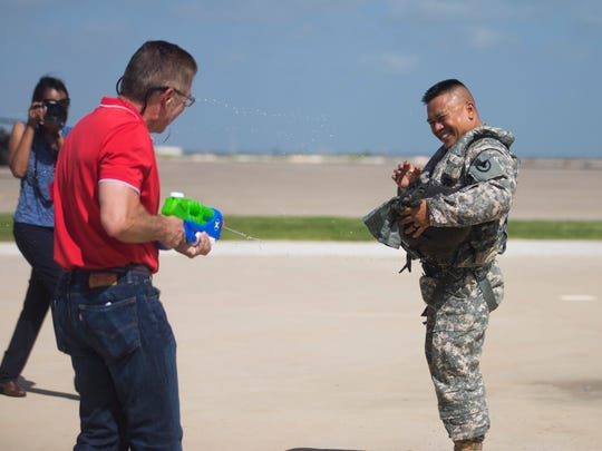 Corpus Christi Army Depot Commander, Colonel Allan H. Lanceta is sprayed with water guns by family and friends after he took his final helicopter flight on Wednesday, July 18, 2018 at the Corpus Christi Army Depot.