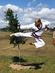 Chief instructor Rodrigo Cruz jump kicks in front of