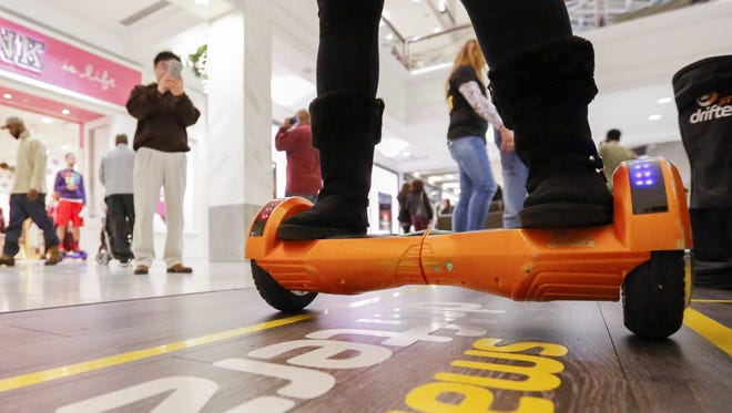Early 'Black Friday' shoppers view a sales person on a hover board self-balancing scooter at the Lenox Square Mall in Atlanta.