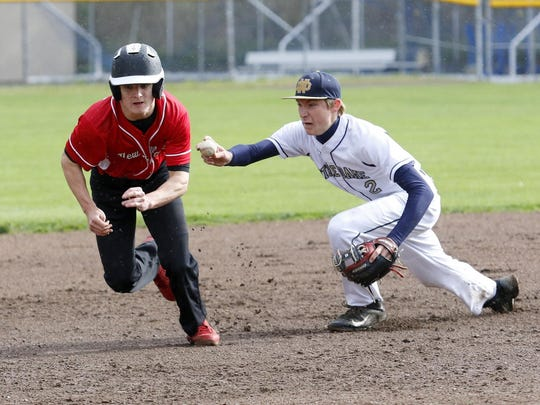 Elmira Notre Dame shortstop Matt Smith reaches out to tag Brett Stewart of Newark Valley after a run down during Wednesday's IAC game in Southport.