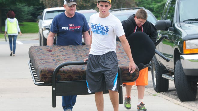 First-year University of Wisconsin-Stevens Point student Dennis Larson of Loyal gets a hand from his father, Don Larson, on move-in day Thursday.