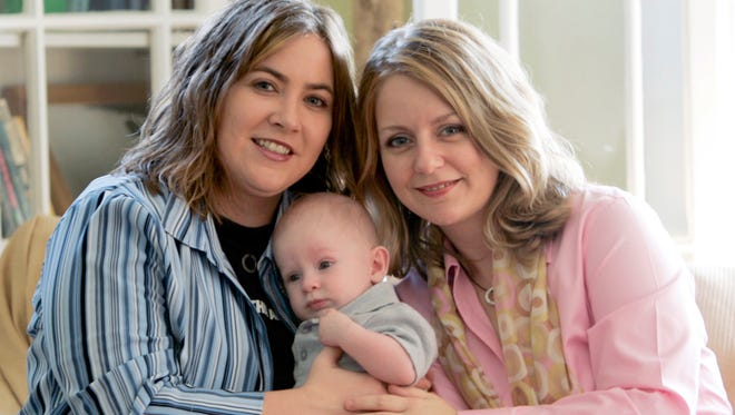 In this May 4, 2006 file photo, Cari Searcy, left, and Kim McKeand pose with their son, Khaya, in Mobile, Ala. Courts refused to let Searcy be recognized as the adoptive parent of the boy.