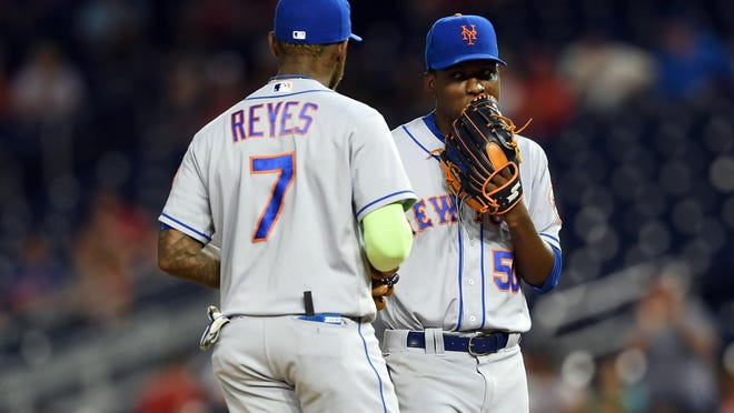 New York Mets third baseman Jose Reyes (left) speaks with starting pitcher Rafael Montero (50) during the first inning Monday against the Washington Nationals on the pitcher's mound at Nationals Park.