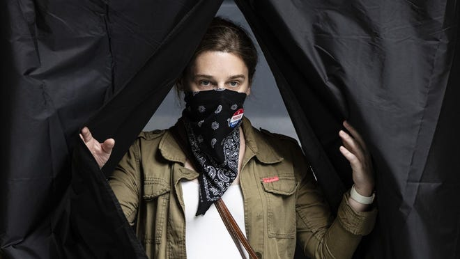Jenn McCullough, wearing a protective face mask as a precaution against the coronavirus, steps from the voting booth after casting her ballot in the Pennsylvania primary at the Kimmel Center in Philadelphia, Tuesday, June 2, 2020.