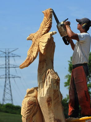 Chad Gainey is in the process of turning a 10-foot stump, 32 inches in diameter, into a carved sculpture anchored at the top by an eagle spreading its wings. TVA officials agreed to leave the tree behind. Gainey, seen working on Thursday, July 31, 2014, plans to add a scene of owls on branches, along with a Dr. Seuss-inspired Lorax at the base, and possibly more. He estimates that his entire project will require 20 hours of work. The stump is on property owned by Dana Duncan.