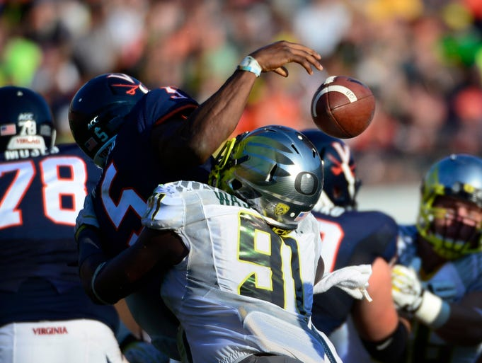 Oregon Ducks defensive end Tony Washington forces Virginia quarterback David Watford to fumble.
