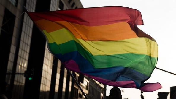 Jesus Palaez waves a rainbow flag at Kentuckiana Pride