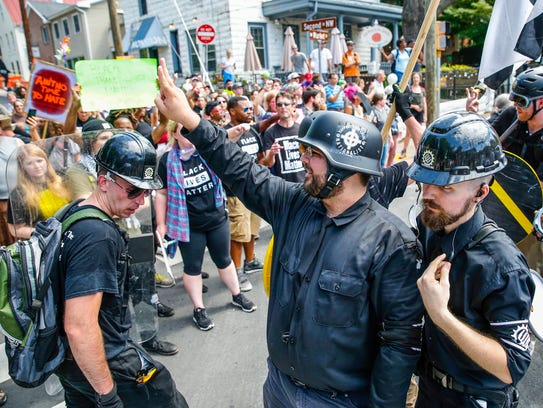 Matt Heimbach, a white nationalist who calls Indiana home, leaves Emancipation Park in Charlottesville, Va. alongside his Traditionalist Worker Party members on Aug. 12, 2017.
