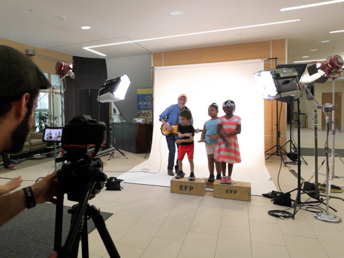 "Local attorney and musician Paul Nunes, center, performs with children from the University of Rochester Warner School of Education's Horizons school for the video for his song ""No Ones Going to Keep Me Down."""