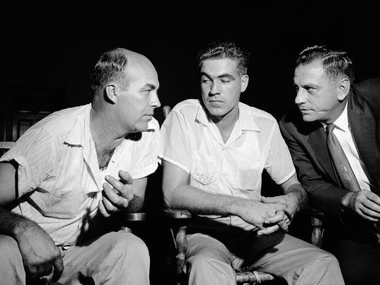 """J. W. Milam, 36, and half-brother Roy Bryant, 24, confer with one of their lawyers J.W. Kellum, right, just before pleding innocent, September 6, 1955 at Sumner, Miss.. They are charged with kidnapping Emmett Till, a 14-year-old Black youth who they claim """"made some remarks"""" and whistled at Bryant's wife. (AP Photo/Gene Herrick)"""