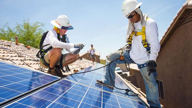 Dylan Robins (left), Michael Armin and Tinh Nguyen install solar panels on a home in Cave Creek. A new interpretation of state law says those who lease arrays face taxes on them.