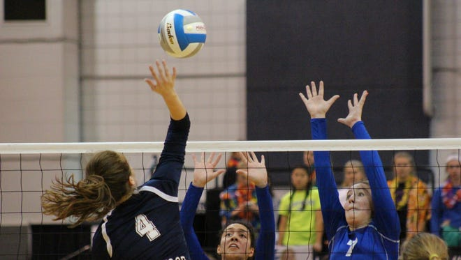 Livonia Ladywood's Samantha Serra (3) and Madison Benoit set up to try blocking a kill by Lake Odessa Lakewood's Breanna Wickerink, in a Class B semifinal at Kellogg Arena on Nov. 17.