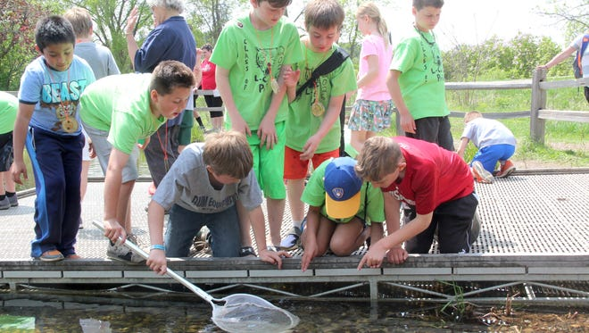 Students use a net to sample aquatic life in a pond during the 2018 Midwest Outdoor Heritage Education Expo at the MacKenzie Center in Poynette, Wis.