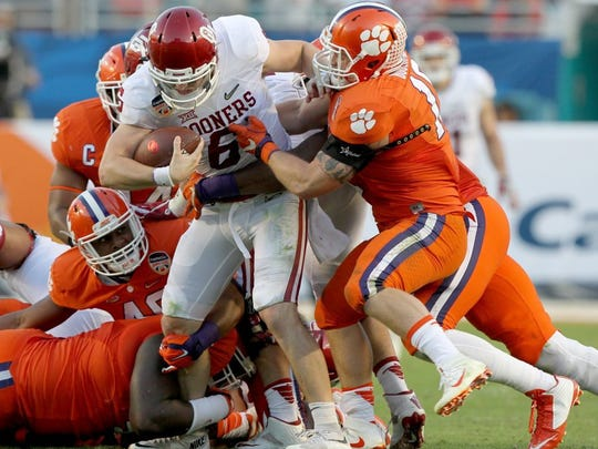 Members of the Clemson defense sack Oklahoma quarterback Baker Mayfield (6).