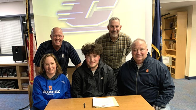 Saugatuck's Tommy Beckman (center) signed with Central Michigan, alongside mother Amy Beckman and father Eric Beckman. Saugatuck football coach Bill Dunn, left) and principal Mark Neidlinger stand in the back row.