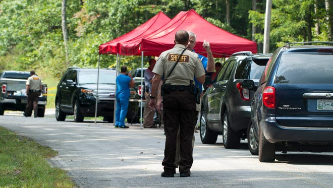 Officials with the Tennessee Bureau of Investigation after the discovery of four bodies in a vehicle Sept. 12, 2013, at the Renegade Mountain resort community near Crab Orchard, Tenn. The Tennessee Bureau of Investigation said four people were been found shot to death in a car in Cumberland County. A resident found the bodies on the way to work after seeing a parked car and going to investigate.