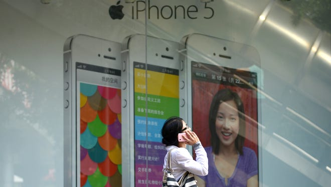A woman uses a mobile phone as she walks past an Apple iPhone 5 poster outside a store in Beijing.