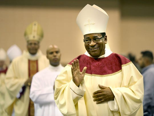 Bishop J. Terry Steib waves to onlookers as he enters