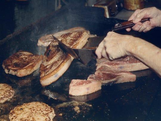 Helen Fisher flips the steaks at the Lowake Steak House