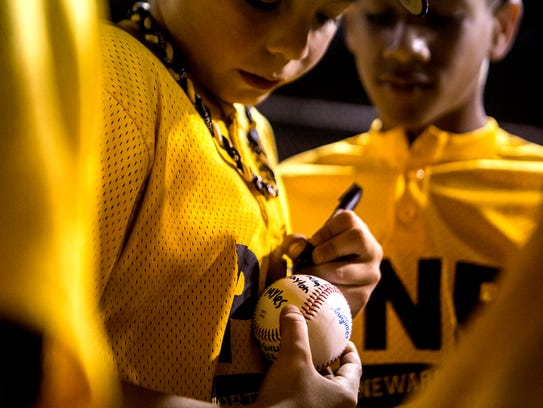 Players from PNB NNLL sign a ball after winning the