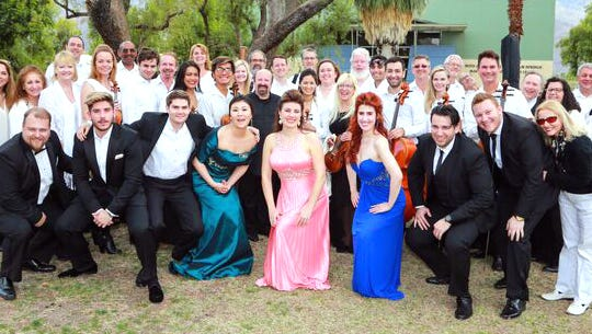 Singers and orchestra ensemble pose together.
