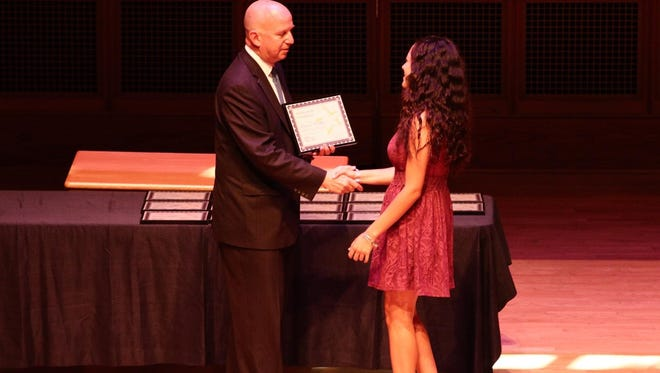 Jack Markell (left) presents a degree to Krystal Mendez, one of the first Delaware College Scholars graduates.