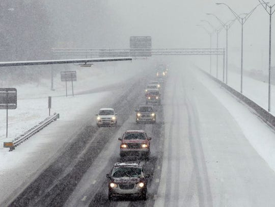 Motorists navigate a snow-covered Interstate 40-85