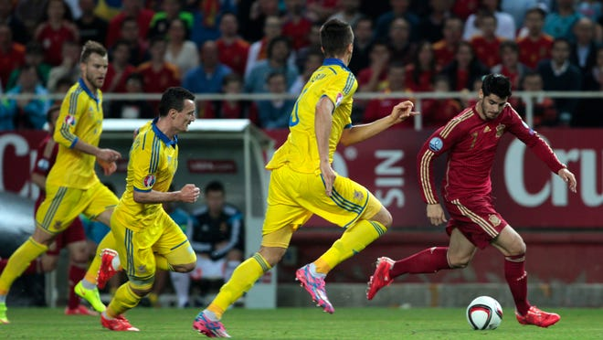 Spain's Alvaro Morata fights for the ball followed by Ukraine's Yevhen Khacheridi, left, during the Euro 2016 qualifying soccer match between Spain and Ukraine, at the Ramon Sanchez Pizjuan stadium, in Seville, Spain, on Friday, March. 27, 2015.