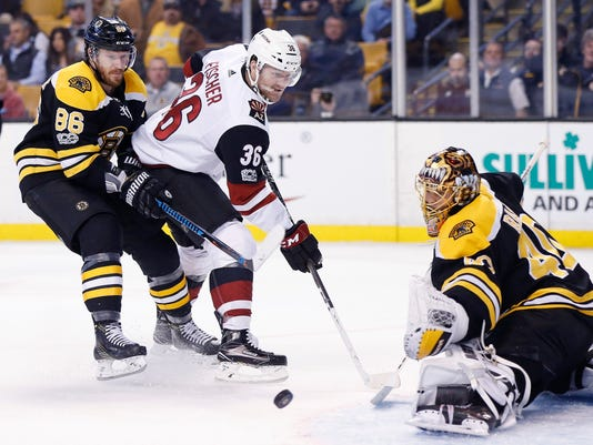 Boston Bruins' Tuukka Rask (40), of Finland, deflects a shot by Arizona Coyotes' Christian Fischer (36) during the third period of an NHL hockey game in Boston, Thursday, Dec. 7, 2017. (AP Photo/Michael Dwyer)