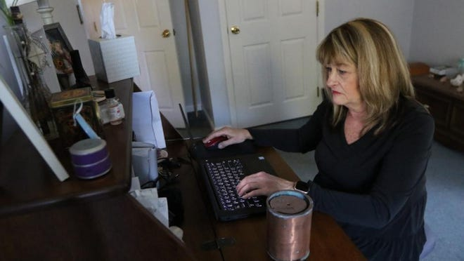 Pam Calder of Shirley, in her home office, is preparing a graveside service for her great-grandmother, Margaret (Fowler) Cutter Willard, who died in 1936. Next to Calder is an urn containing her ancestor's ashes. The urn was forwarded to Calder from Oregon State Hospital.
