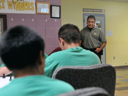 Corrections services officer Art Perea watches youths