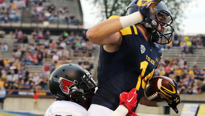 Toledo WR Justin Olack (14) makes a catch for a first down against Ball State CB Tyree Holder (33) during the first quarter Ball State's 34-23 loss.