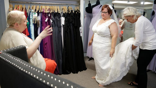 B. Ella Bridal shop owner Brittany Blase, left, helps April DeBoer as she tries on wedding dresses with the help of her her mother Wendy DeBoer at the shop in Plymouth on Tuesday July 14, 2015.
