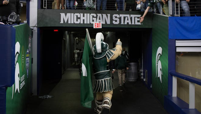 Sparty walks off the field lifting a finger to the fans after Michigan State lost 38-0 against Alabama, at the Goodyear Cotton Bowl Classic in Arlington, Texas on Thursday, Dec. 31, 2015.