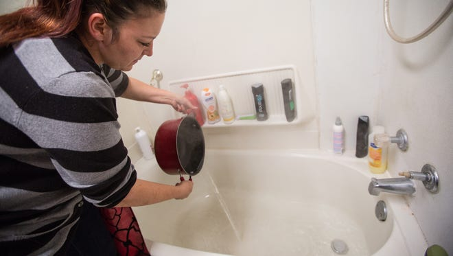 Lee Anne Walters of Flint pours a heated gallon of bottled water into the bath tub for her two sons to take a weekly bath on Thursday, Oct. 1, 2015.