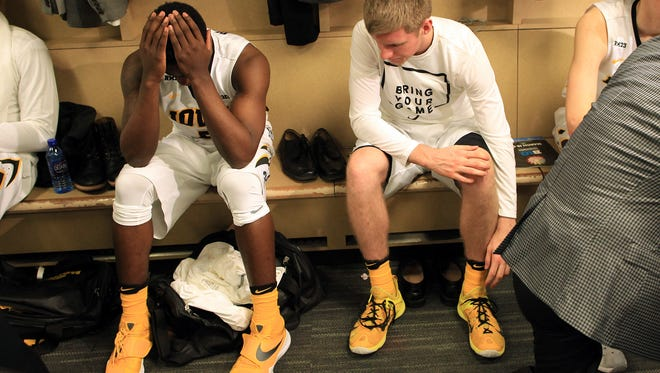 Iowa's Anthony Clemmons, left, sits in the locker room following the Hawkeyes' 68-66 loss to Illinois at the Big Ten Men's Basketball Tournament at Bankers Life Fieldhouse in Indianapolis, Ind. on Thursday, March 10, 2016.